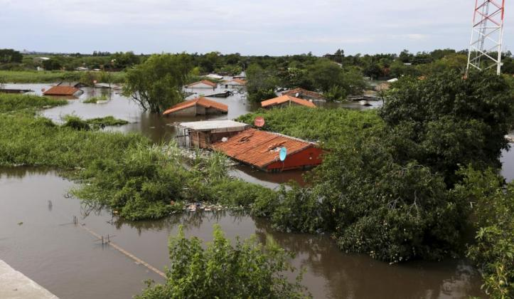 Houses are seen partially submerged in floodwaters in Asuncion, December 27, 2015. REUTERS/Jorge Adorno
